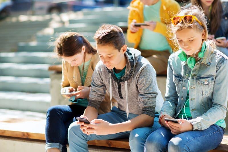 Amici adolescenti con gli smartphones all'aperto fotografia stock