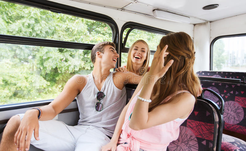 Amici adolescenti felici che viaggiano in bus fotografia stock libera da diritti