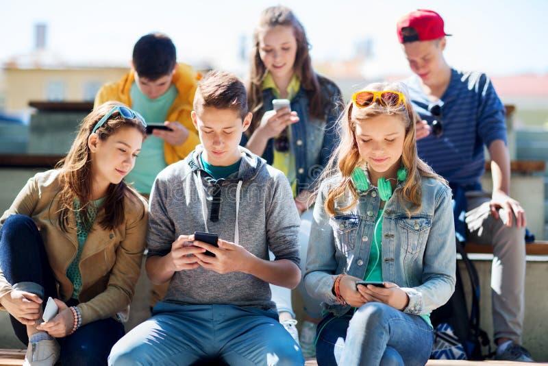 Amici adolescenti felici con gli smartphones all'aperto fotografia stock