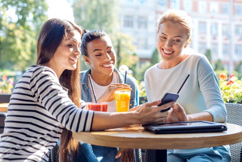 Amici affascinanti che prendono insieme un selfie in caffè fotografie stock libere da diritti