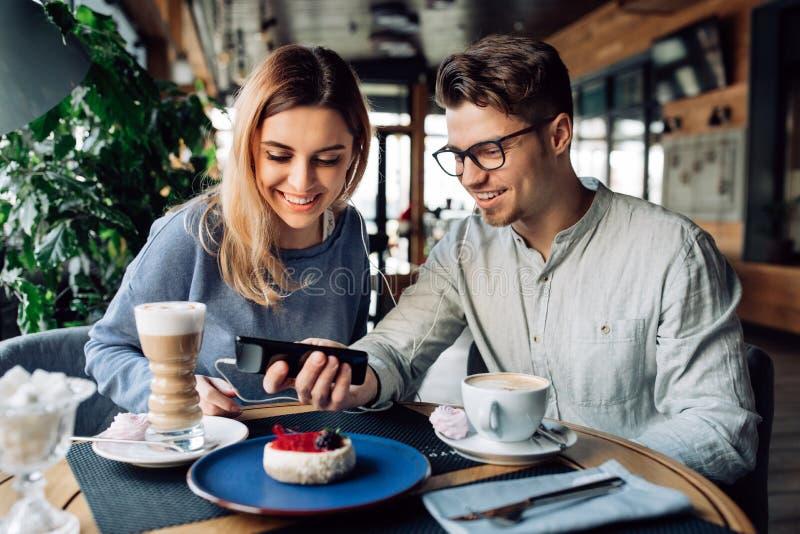 Amici allegri che guardano un film sullo smartphone mentre riposando al caffè immagini stock libere da diritti
