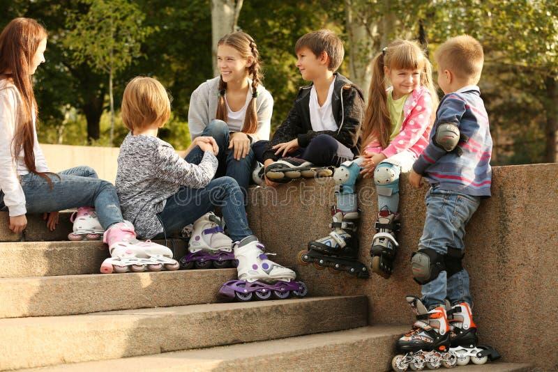 Amici allegri nei pattini di rullo che si siedono sul confine immagini stock