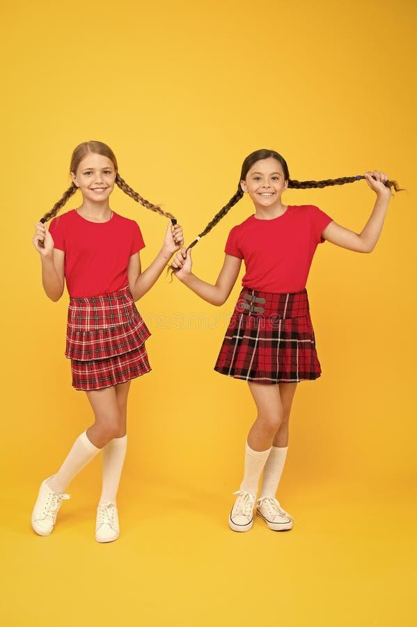 Amici allegri Ragazze piccole che indossano gli stessi vestiti Amici che si divertono Bambini in gamba Felice di essere felice in fotografia stock libera da diritti