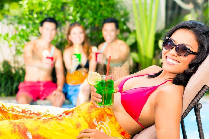 Amici asiatici che fanno festa alla festa in piscina nella località di soggiorno fotografie stock