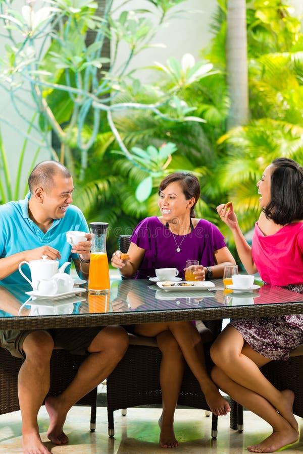 Amici asiatici che mangiano caffè sul portico domestico fotografie stock