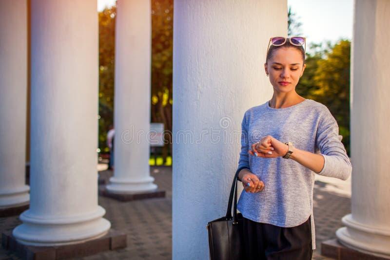 Amici aspettanti dello studente di college in parco Giovane donna che controlla tempo che esamina orologio immagine stock libera da diritti