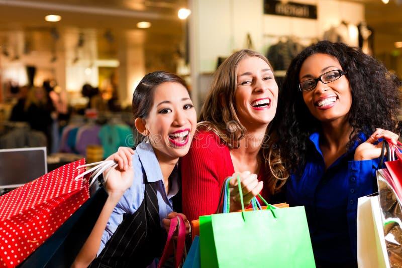 Amici che acquistano con i sacchetti in viale immagine stock libera da diritti