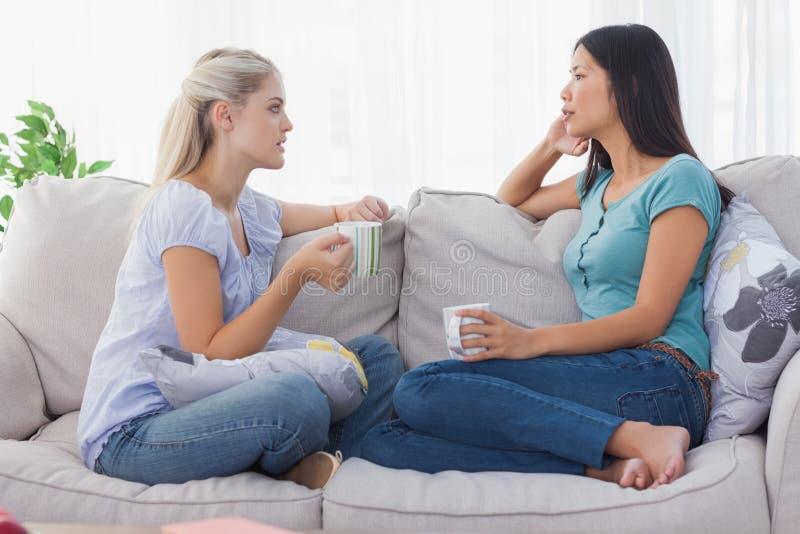 Amici che bevono caffè e che hanno una chiacchierata seria immagine stock