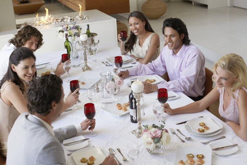 Amici che bevono e che socializzano al partito di cena immagini stock libere da diritti