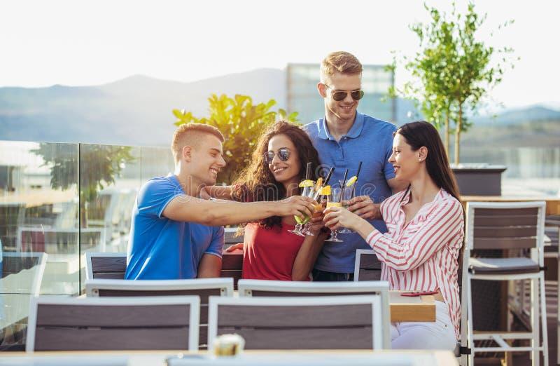 Amici che bevono i cocktail all'aperto su un balcone dell'attico fotografia stock libera da diritti