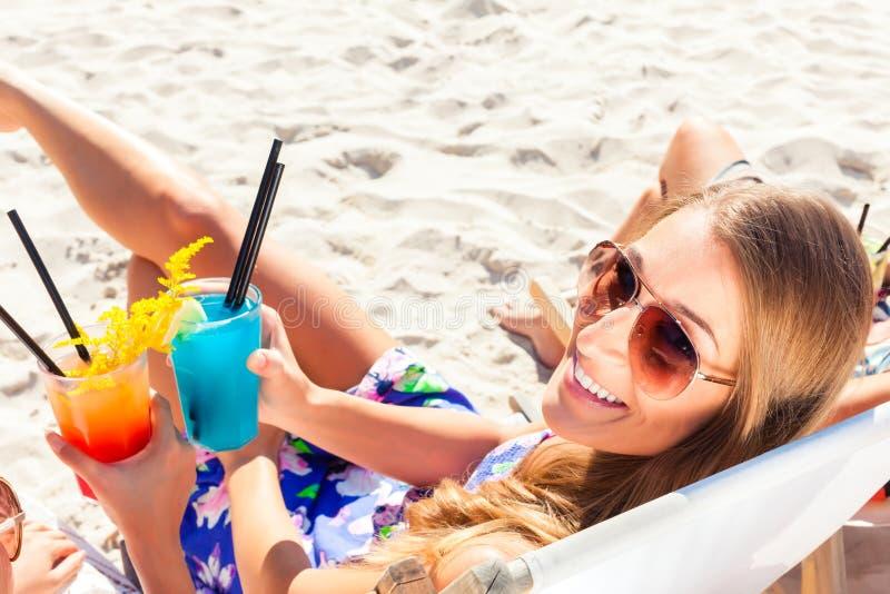 Amici che bevono i cocktail nella barra della spiaggia immagini stock libere da diritti