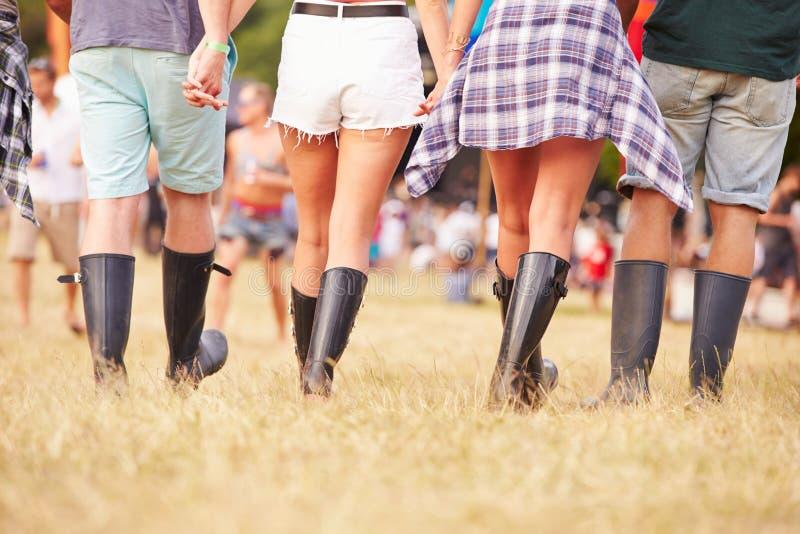 Amici che camminano insieme ad un sito di festival di musica, vista posteriore fotografia stock
