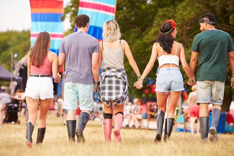 Amici che camminano insieme ad un sito di festival di musica, vista posteriore immagini stock
