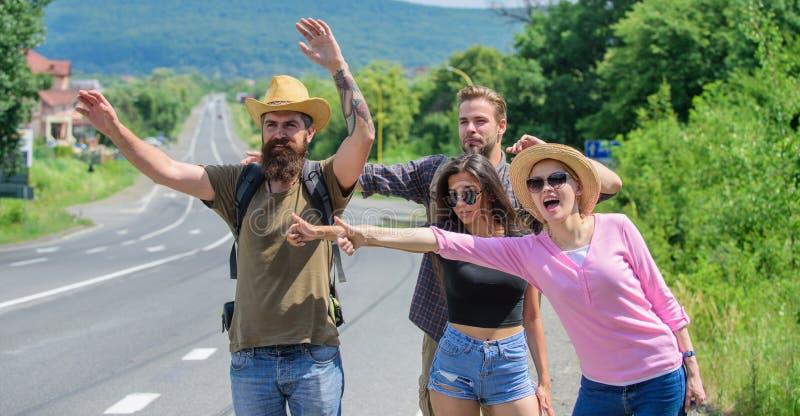 Amici che cercano trasporto Giorno soleggiato di viaggio degli autostoppisti degli amici Cominci la grande avventura nella vostra fotografia stock libera da diritti
