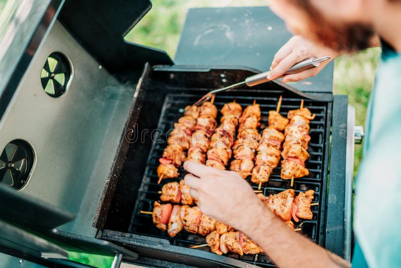 Amici che cucinano sulla griglia durante l'estate Ritratto dell'uomo che griglia e che ha un partito del barbecue del giardino fotografie stock
