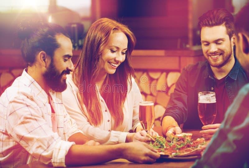 Amici che dividono pizza con la birra alla pizzeria fotografia stock libera da diritti