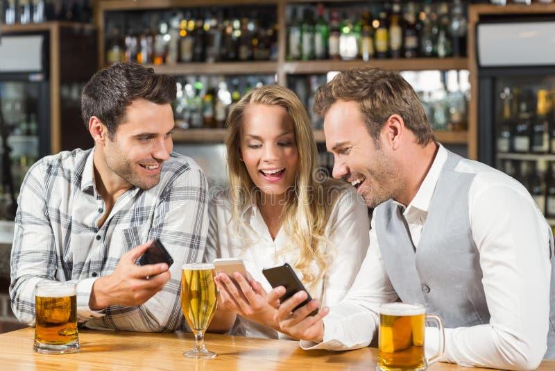 Amici che esaminano gli Smart Phone fotografia stock