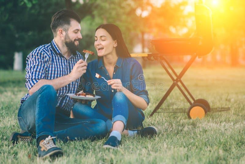 Amici che fanno barbecue e che pranzano nella natura Coppia divertiresi mentre mangiano e bevendo ad un picnic - felice immagine stock