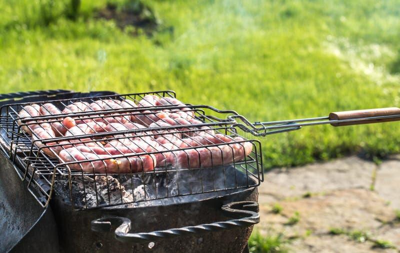 Amici che fanno barbecue e che pranzano nella natura immagine stock libera da diritti