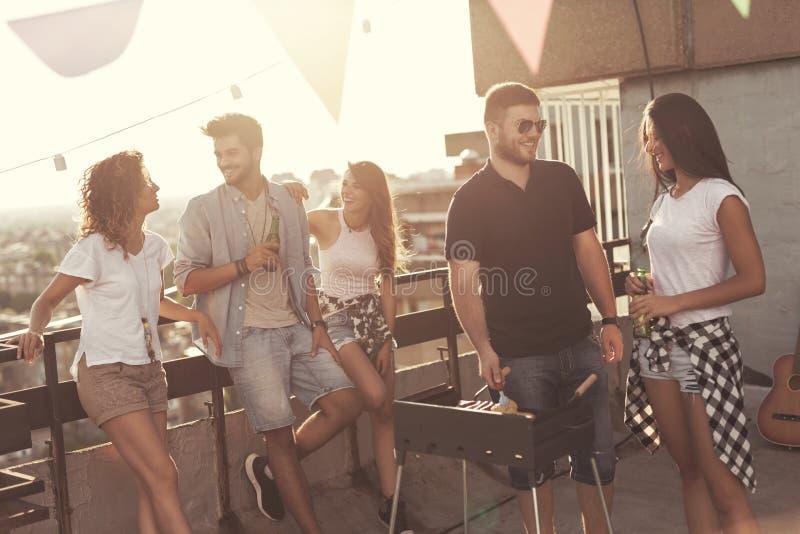 Amici che fanno il barbecue del tetto fotografie stock libere da diritti