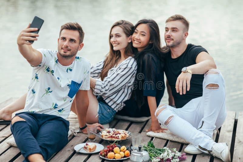 Amici che fanno selfie che si siede sul pilastro con il fondo del lago mentre fotografia stock libera da diritti