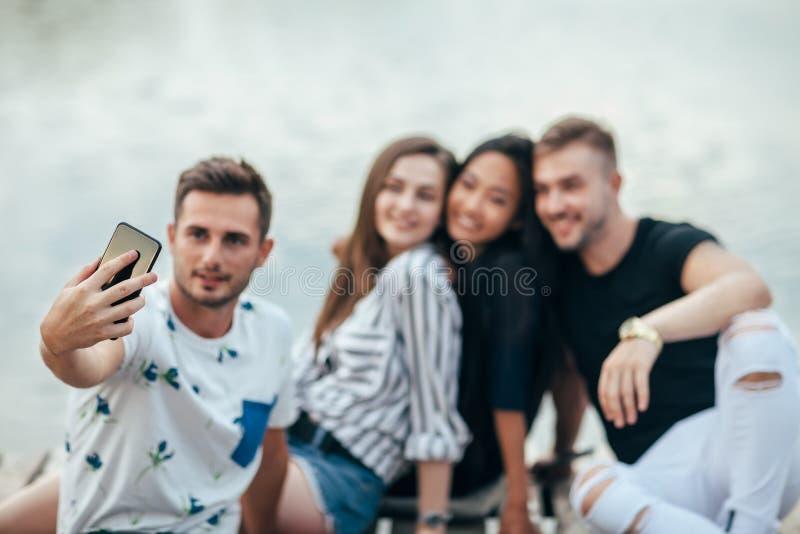 Amici che fanno selfie che si siede sul pilastro con il fondo del lago mentre immagini stock libere da diritti