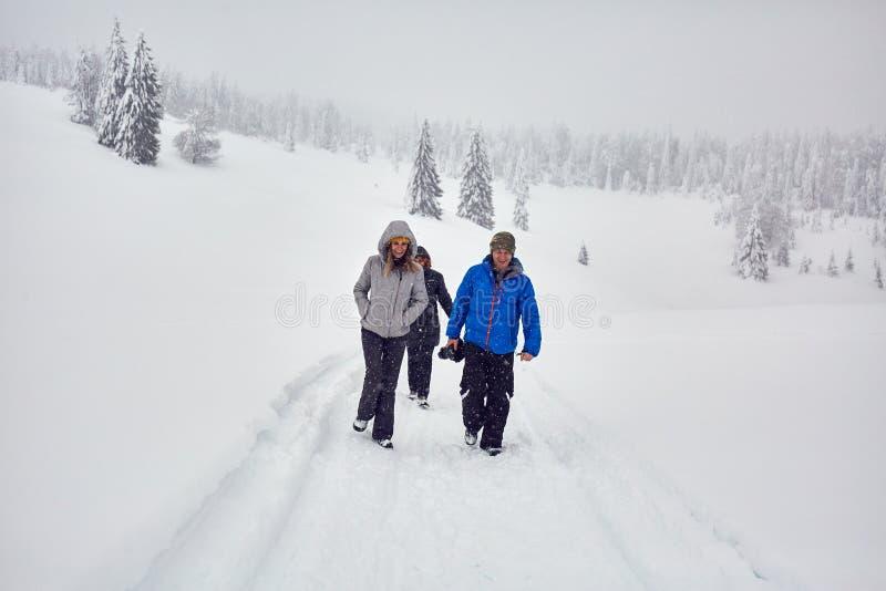 Amici che fanno un'escursione su una traccia nevosa immagine stock