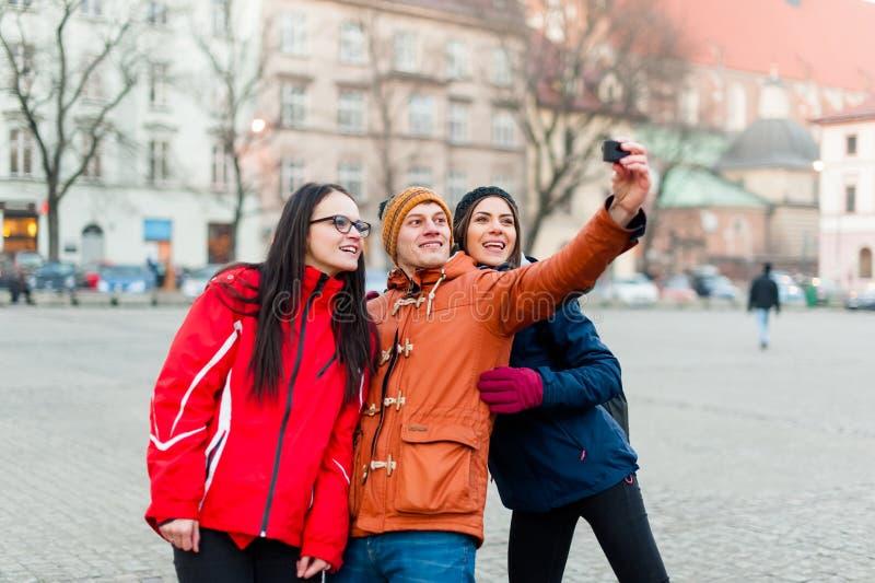 Amici che fissano i selfies con la macchina fotografica portabile in una città turistica immagini stock libere da diritti