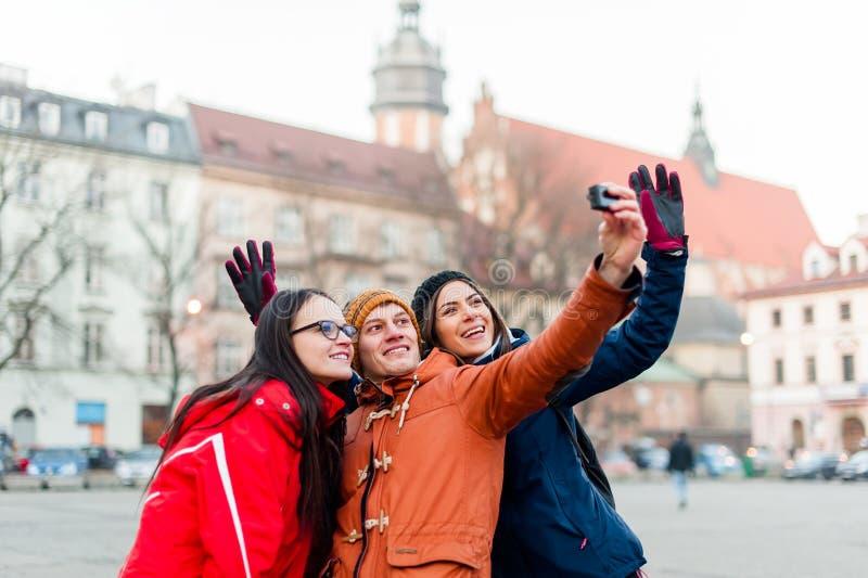 Amici che fissano i selfies con la macchina fotografica portabile in una città turistica fotografia stock