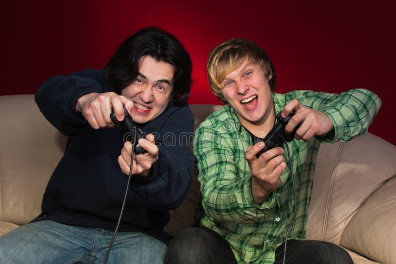 Amici che giocano i video giochi fotografie stock