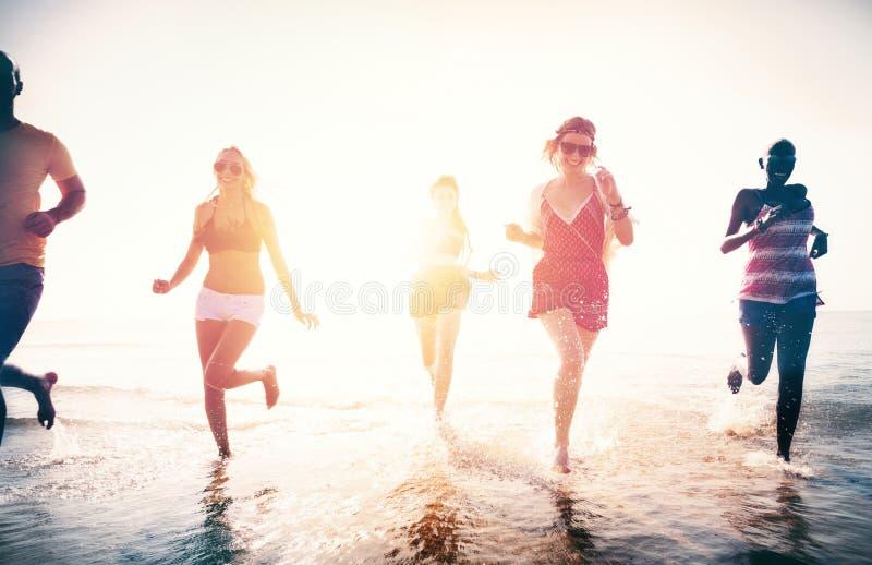 Amici che giocano nell'acqua alla spiaggia immagini stock libere da diritti