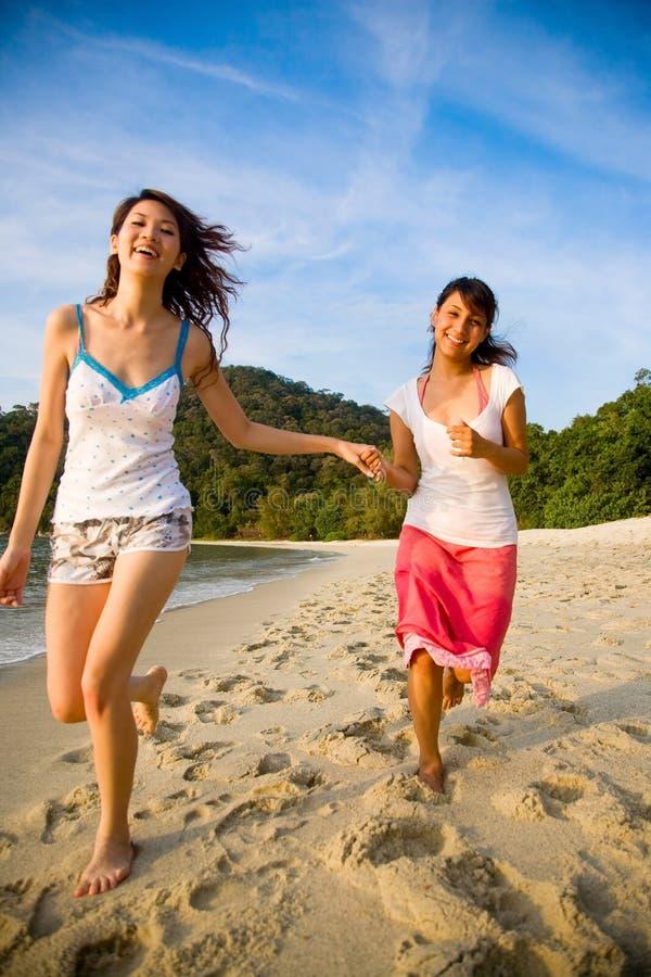 Amici che hanno divertimento funzionare lungo la spiaggia fotografie stock libere da diritti
