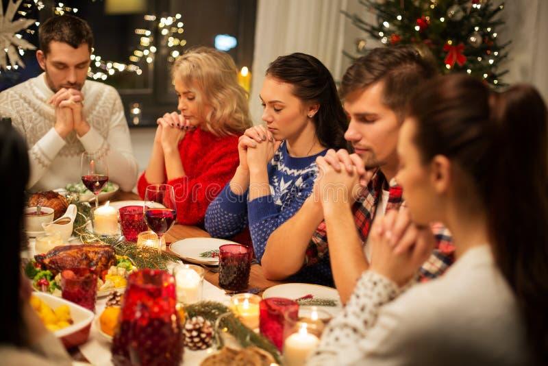 Amici che hanno la cena e pregare di natale domestica immagine stock libera da diritti