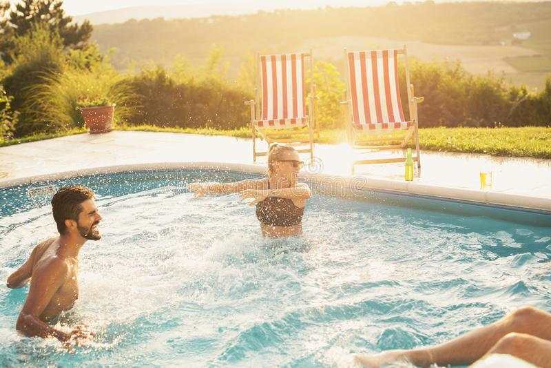 Amici che hanno un'acqua che spruzza divertimento ad uno stagno fotografia stock libera da diritti