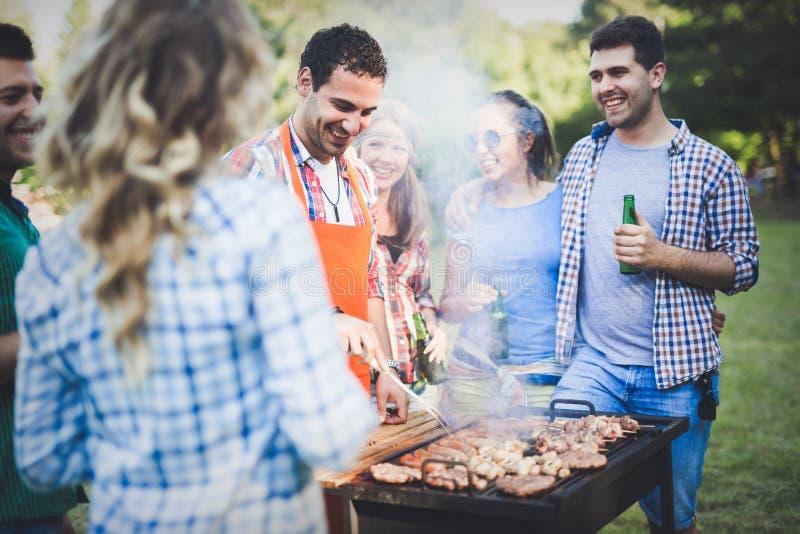 Amici che hanno un partito del barbecue in natura fotografie stock