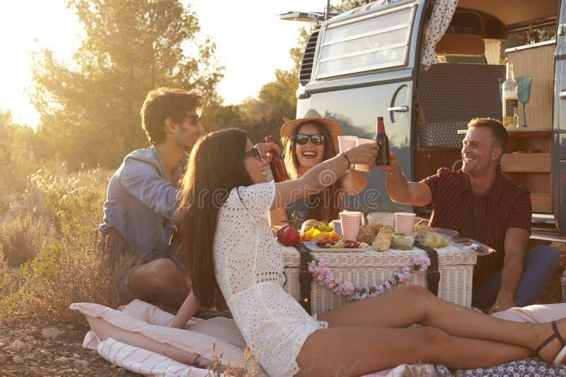 Amici che hanno un picnic accanto ad un camper che produce un pane tostato fotografia stock libera da diritti
