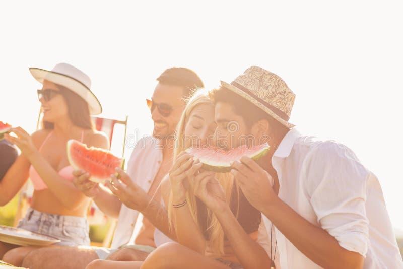 Amici che mangiano anguria alla piscina immagine stock libera da diritti