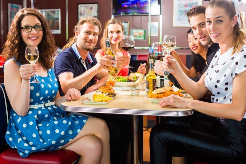 Amici che mangiano e che bevono nella cena degli alimenti a rapida preparazione immagini stock libere da diritti