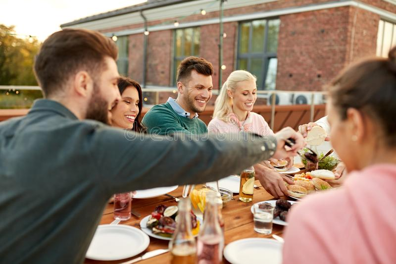 Amici che mangiano gli hamburger al partito di cena sul tetto immagine stock
