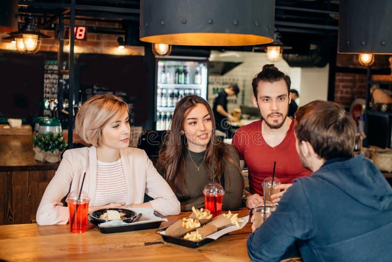 Amici che mangiano insieme le patate fritte e gli hamburger al ristorante all'aperto sotto il sole di estate immagine stock