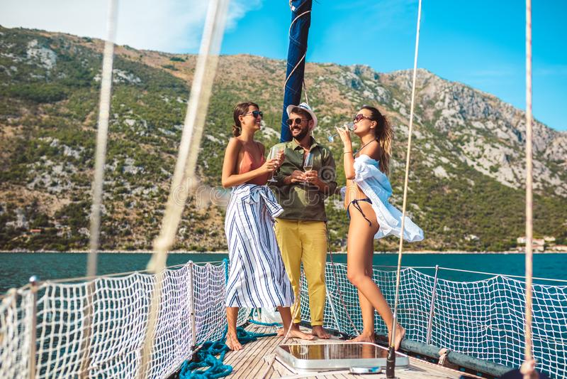 Amici che navigano sull'yacht - vacanza, viaggio, mare, amicizia e concetto della gente immagini stock