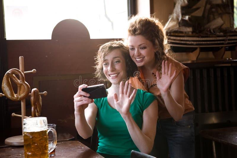 Amici che ondeggiano allo smartphone fotografia stock