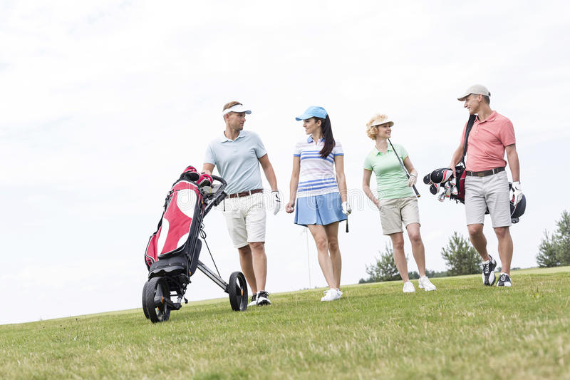 Amici che parlano mentre camminando al campo da golf contro il chiaro cielo fotografie stock libere da diritti
