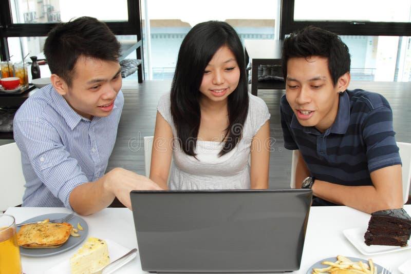 Amici che per mezzo di un computer portatile fotografia stock libera da diritti