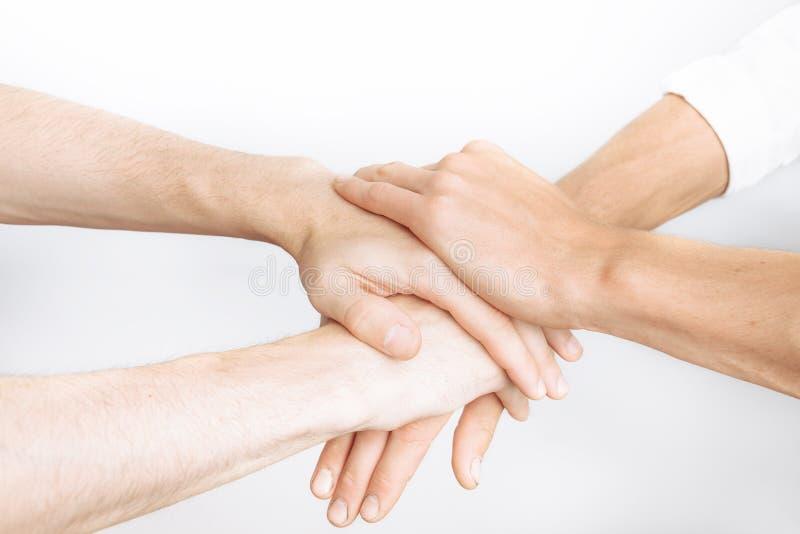 Amici che pregano insieme, come un gruppo, successo, vittoria, fondo bianco fotografia stock