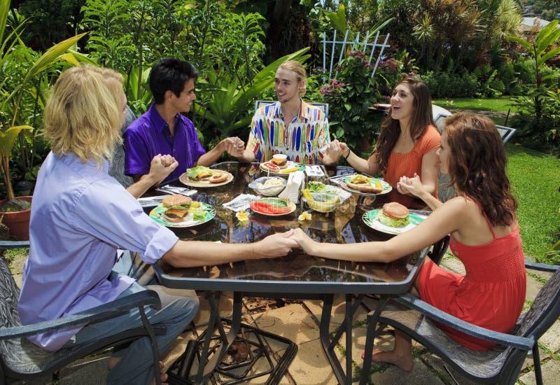 Amici che pregano insieme prima di pranzare fotografia stock