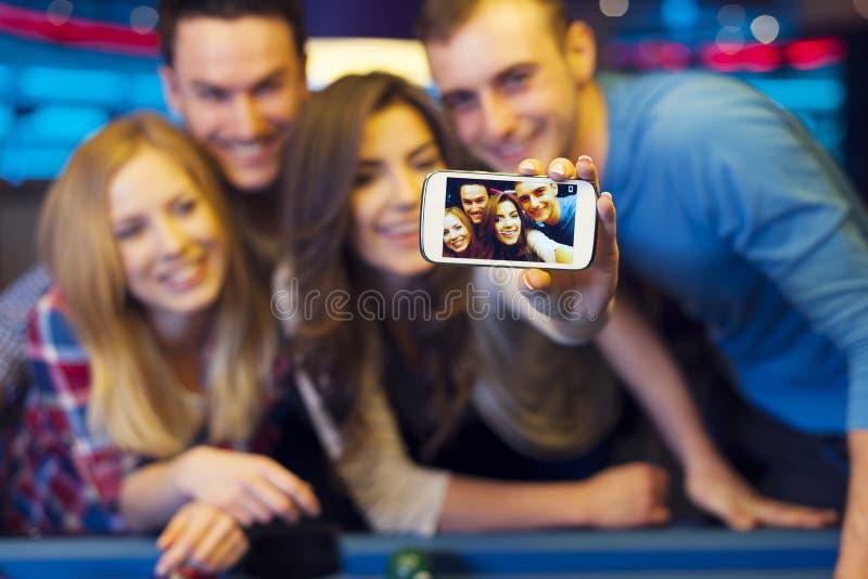 Amici che prendono autoritratto sul telefono cellulare fotografia stock libera da diritti