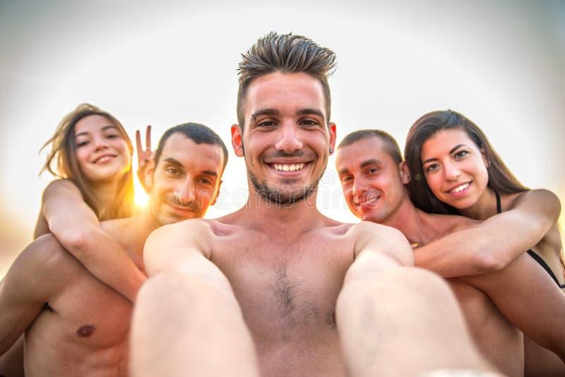 Amici che prendono un selfie sulla spiaggia immagine stock
