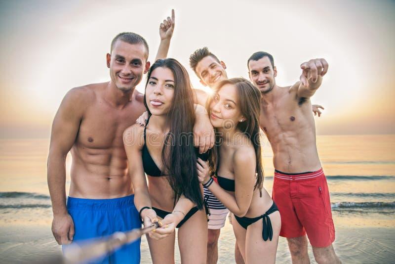 Amici che prendono un selfie sulla spiaggia immagine stock libera da diritti