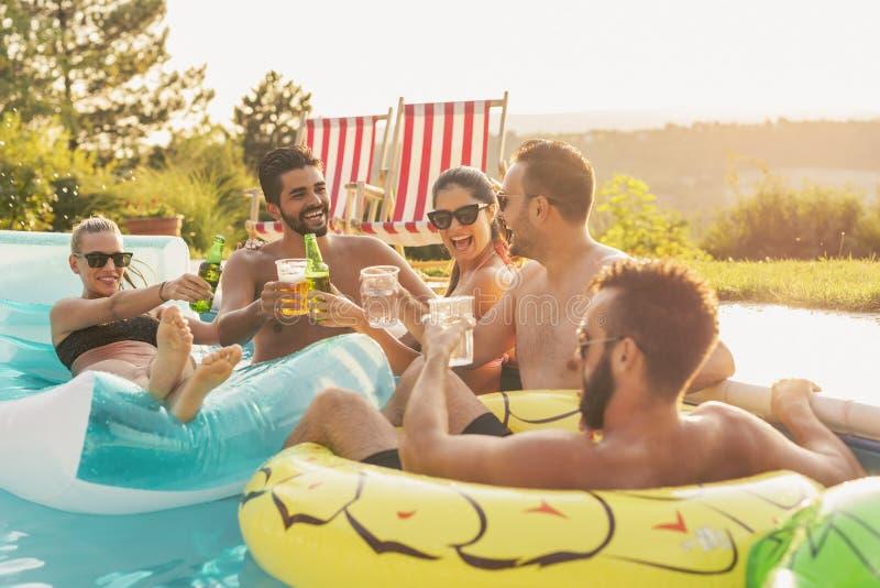 Amici che producono un pane tostato ad un partito del poolside immagine stock libera da diritti
